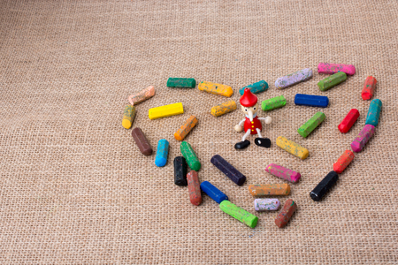 pinocchio in the middle of crayons form a heart shape