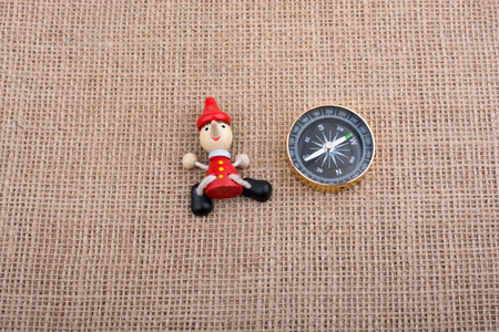 Figurine of pinocchio  by the side of a compass