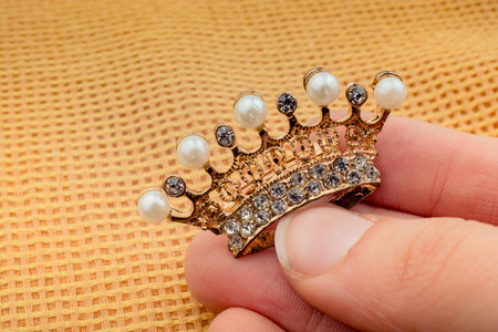 Hand holding a little model crown in hand