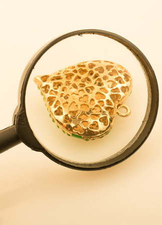 Heart shaped gold color metal under magnifying glass