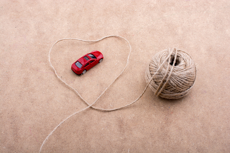 TRed toy car and a spool of thread form a heart shape on background