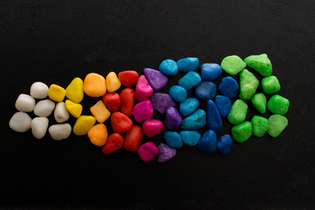 Pile of little colorful pebbles on black background