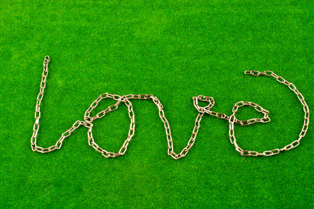 Chain writes the word love on green grass 스톡 콘텐츠