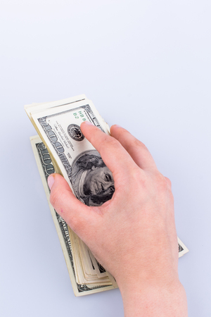Human hand holding American dollar bill as money isolated on white