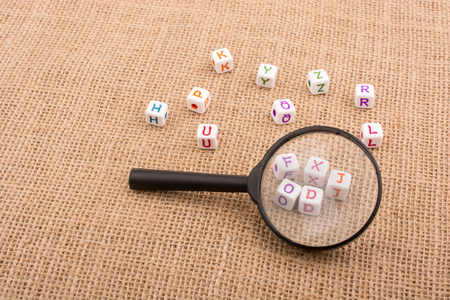 Colorful alphabet letter cubes behind a magnifying glass