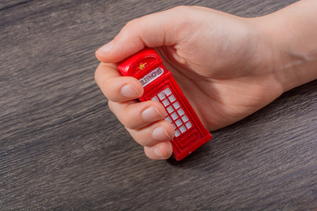 Hand holding a phone booth on a brown background Stockfoto