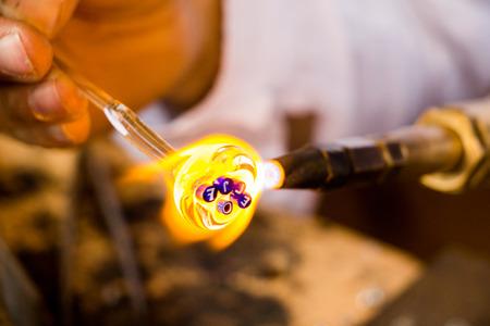 Handen van een man die een glazen onderwerp maakt tentoongesteld