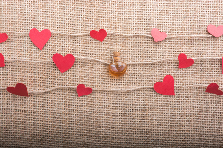 Heart shaped bottle and papers on linen threads