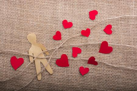 Icone di carta uomo e cuore su fili di lino su tela