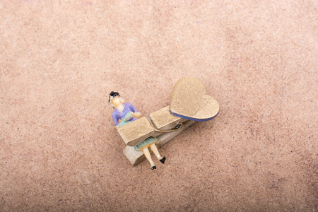 Woman figurine trapped in a clothespin on ground