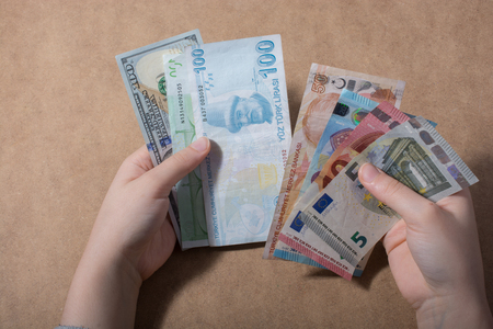 Hand holding American dollar and Euro banknotes on wooden background