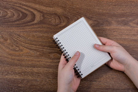 White notebook in hand on  a brown color background Imagens