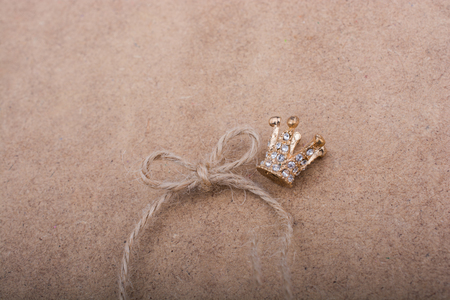 Golden color crown model with pearls on brown background