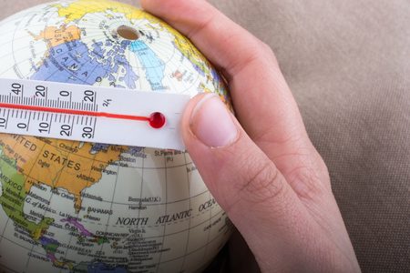 Hand placing a thermometer on a little model globe Stockfoto