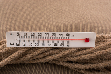 Thermometer placed on a brown rope on a fabric background Stockfoto