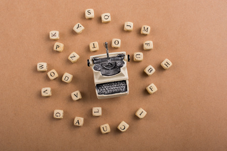 Letter cubes of made of wood around model typewritter