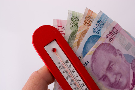 Turkish Lira banknotes by the side of a red color temperature on white background