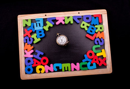 Pocket watch and colorful Letters of Alphabet made of wood