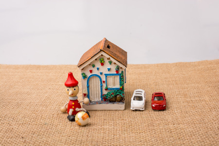 Little model house with cars and Pinocchio