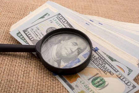 Magnifying glass is held over the banknote bundle of US dollar Stock fotó