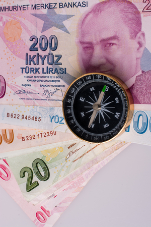 Turkish Lira banknotes by the side of a compass on white background