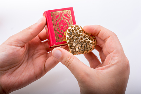 Hand holding Heart shape  and Islamic Holy Book Quran