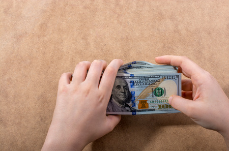 Hand holding American dollar banknotes isolated on wooden background