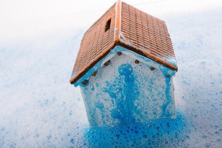 Little model house   and a painting brush in foamy water