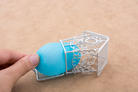 Little yellow balloon placed in a blue color bird house with metal bars Imagens