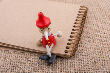 Pinocchio sitting on notebook on a canvas background