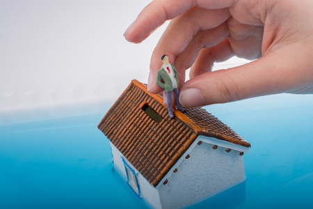 Hand holding a man   figurines in water by on the roof of  a model house