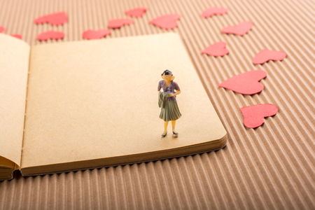 Woman figurine on notebook with red paper hearts around