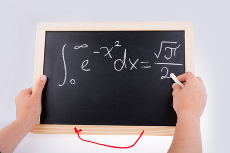 Hand writing a math problem on board with  a chalk