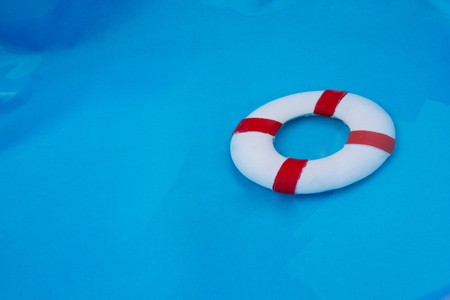 Little red and white color model life buoy in water