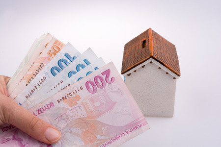 Hand holding Turkish Lira banknotes by the side of a model house on white background