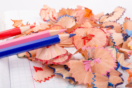 color pencils with its shavings on white background