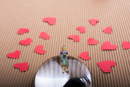 Woman figurine and Love concept with red paper hearts