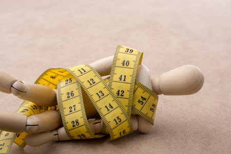 Yellow color measuring tape wrapped on wooden man