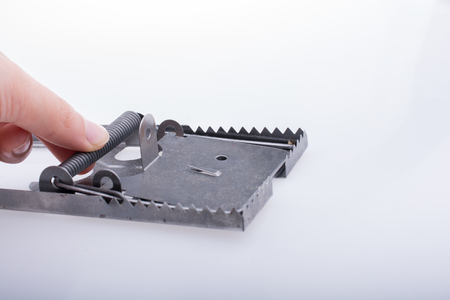 Hand pressing on a steel mouse trap in a white background on display Stock fotó