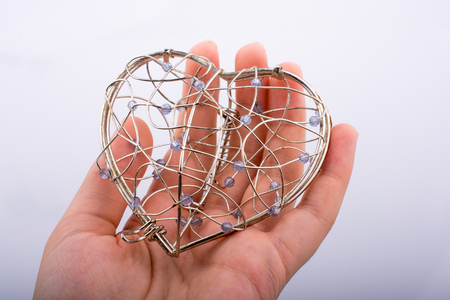 Heart shaped silver color metal wire cage in hand