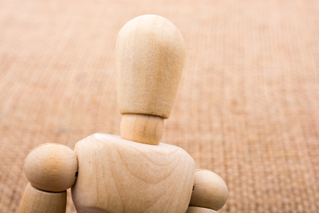 Wooden dolls of a man posing on canvas