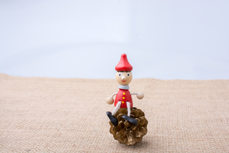 Wooden Pinocchio doll sitting on pine cone on canvas