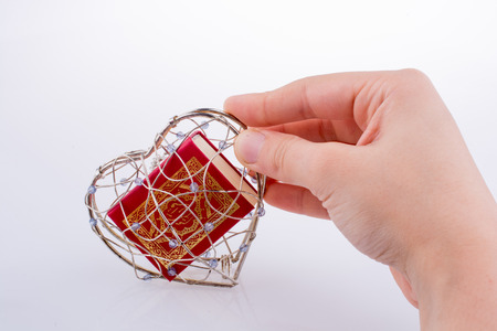 The Holy Quran in a heart shaped cage on a white background Stock Photo