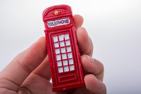 Hand holding a red color phone booth on a white background