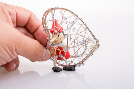 Wooden Pinocchio doll sitting in a heart shaped cage Stockfoto