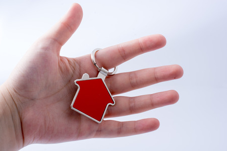 Real estate concept with a metal house icon in hand