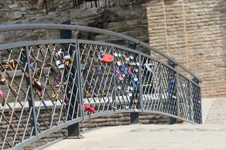 Many colorful metal love padlocks on fence