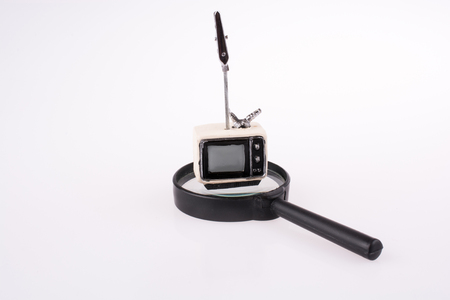 Retro styled television set on a  magnifying glass on white background