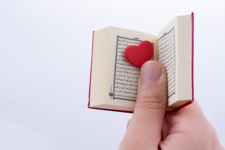 Hand holding The Holy Quran with a heart on a white background Stock Photo