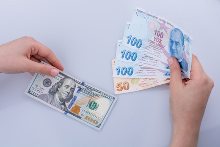 Hands holding American dollar banknotes and Turksh Lira banknotes side by side on white background Stock fotó